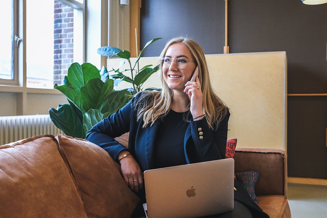 business woman talking on the phone while working on a laptop