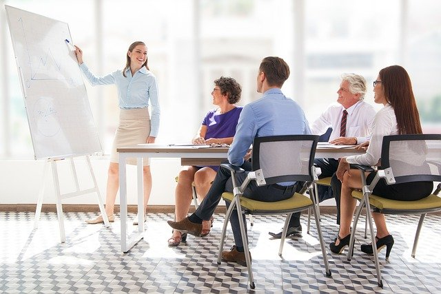 Woman giving business management training to group of people in a conference room